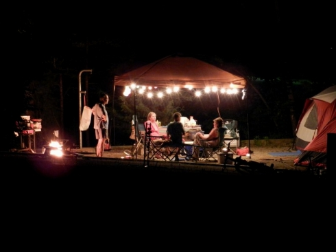 photograph of a family gathering at a campsite after dark