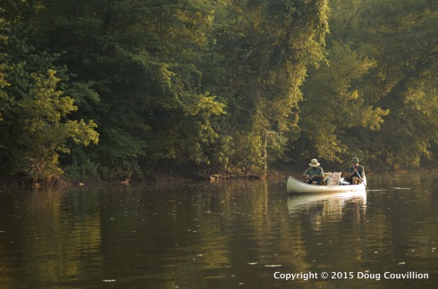 photograph of two men paddling a canoe on the Rappahannock River in the late evening light