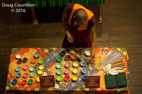 photograph of a Tibetan monk getting colored sand to use for a mandala