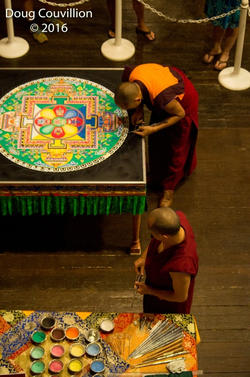 photograph of two Tibetan monks working on a mandala