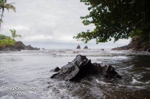 Photography by Doug Couvillion: Landscape of a small volcanic rock in the foreground and larger volcanic rocks, offshore, in the background